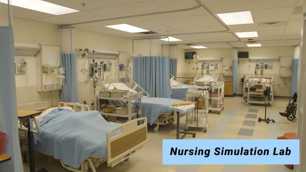 Photo of nursing simulation lab showing a medical room lined with beds occupied by simulation dummies.