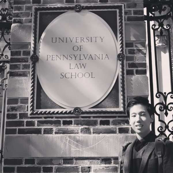 Chan Woo standing next to a sign that says University of Pennsylvania Law School.