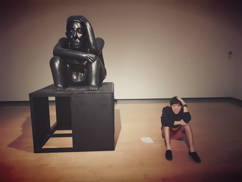 Hojun sitting next a statue imitating it with his hand on his head.