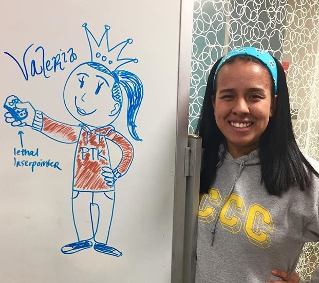 Velaria standing next to a white board with a drawing on it.