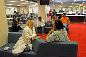 Students sitting in the learning commons chatting.