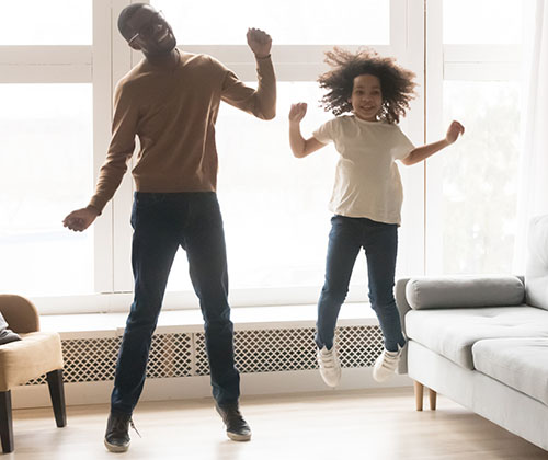 Father and daughter jumping in living room