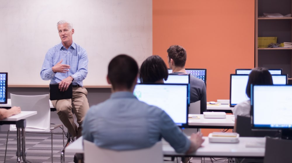 Instructor talking to students on computers