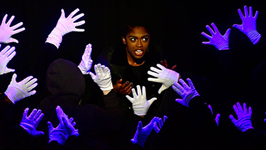 Actor on stage surrounded by white gloves.