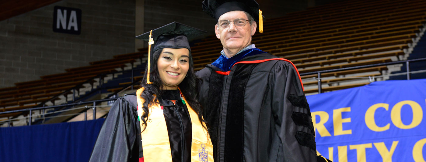 President Parker with student at graduation.
