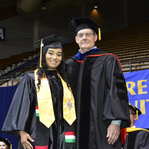 President Jerry Parker poses with grad