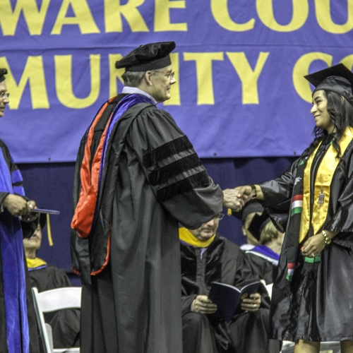 Graduate walks across the stage, shakes hands with college officials