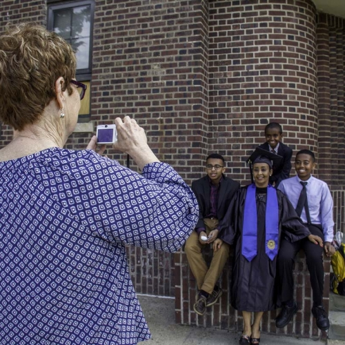 Woman taking photo of student posing for picture with loved ones