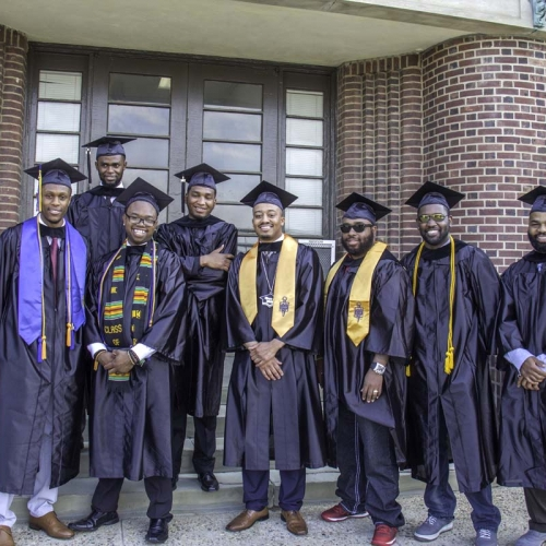 Students in cap and gown posing for photo