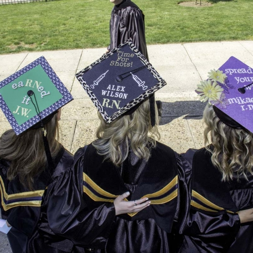 Students with customized caps in green, black and purple colors
