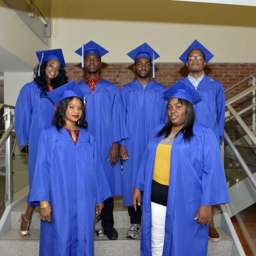 Graduates posing on staircase in the STEM building.