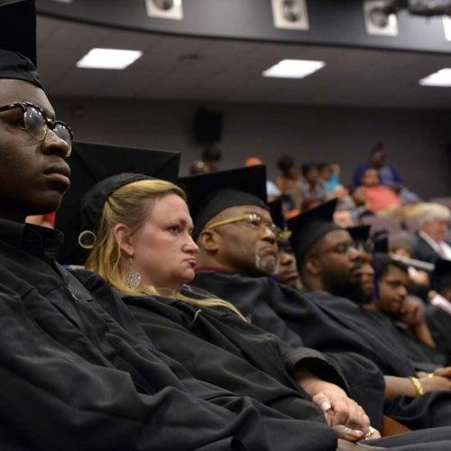 Graduates listening to speach in auditorium.