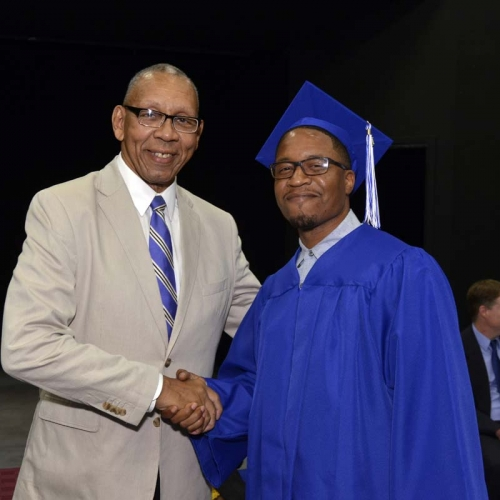 Graduate shaking hands with man.