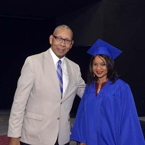 Graduate posing with man.