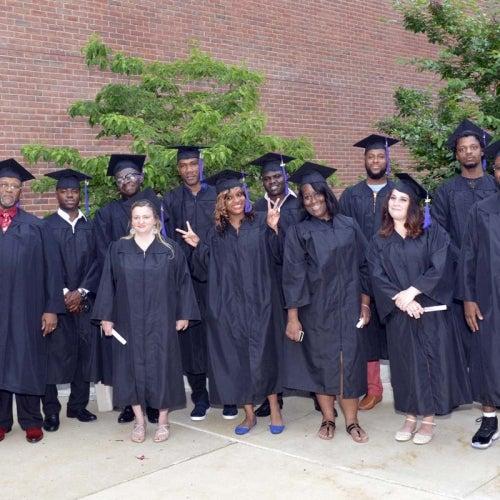 Graduates posing outside.