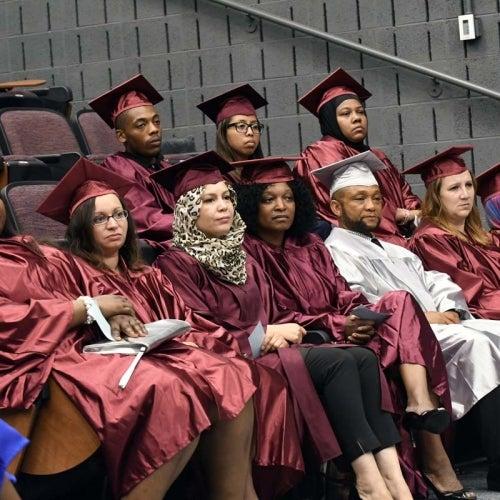 Graduates seated in auditorium.