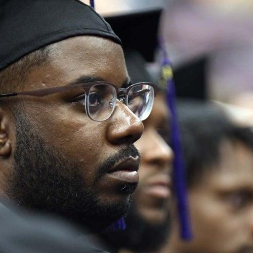 Graduate in auditorium listening to speach.