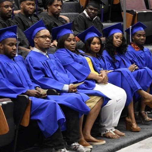 Gradates in auditorium listening to speach.