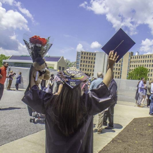 Grad holds up flowers and diploma
