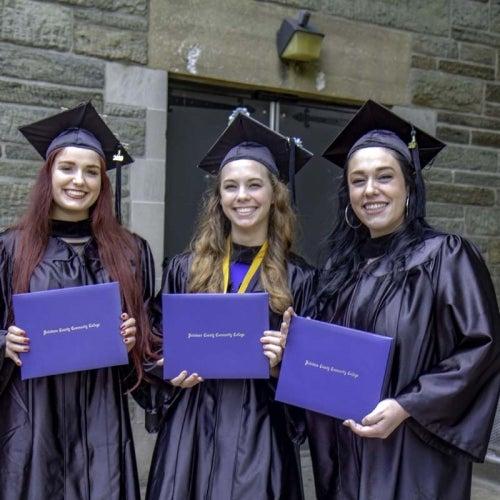 Three graduates pose with diplomas